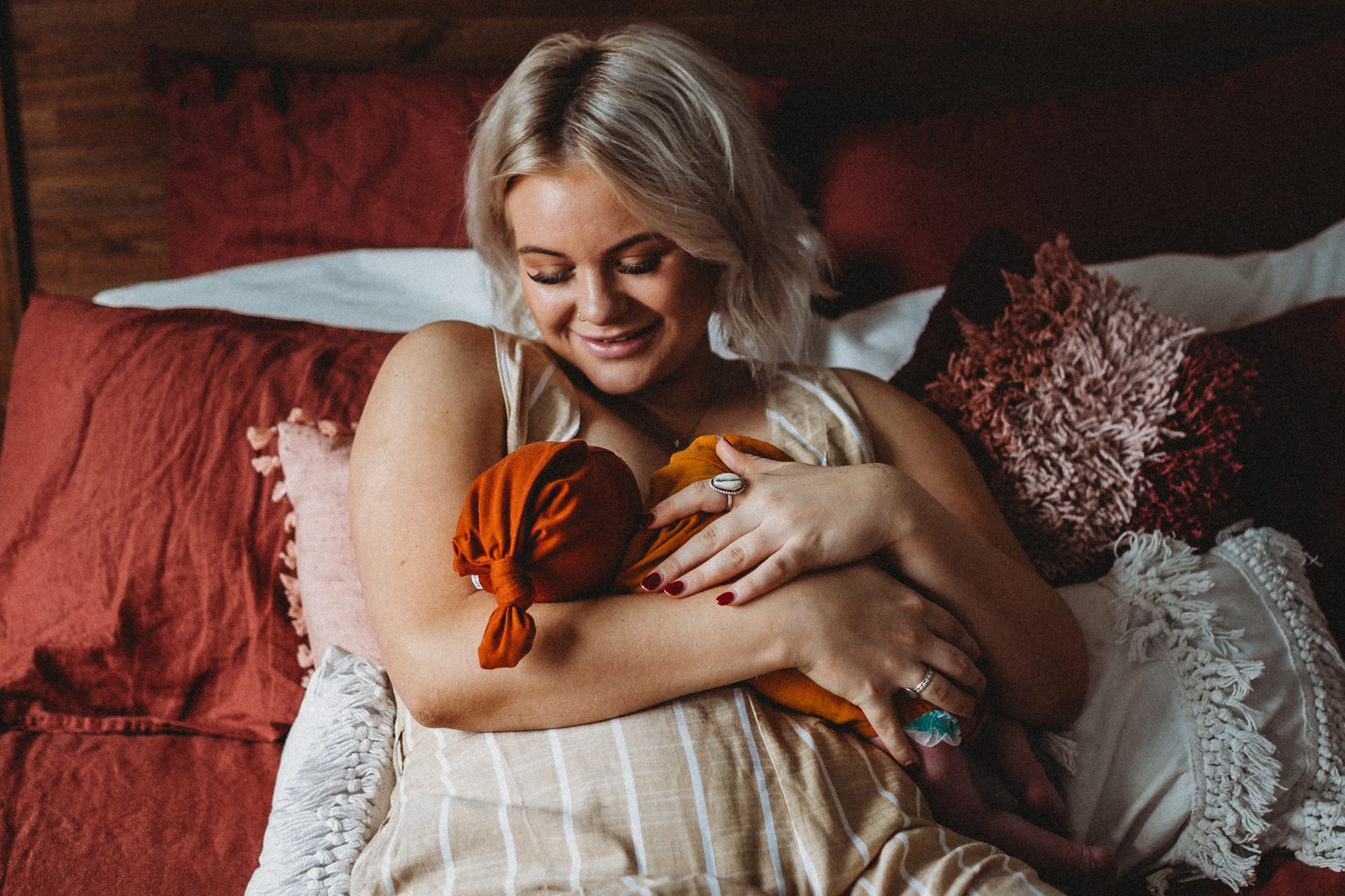 Young woman leaning back on pillows, smiling down at newborn son while breastfeeding