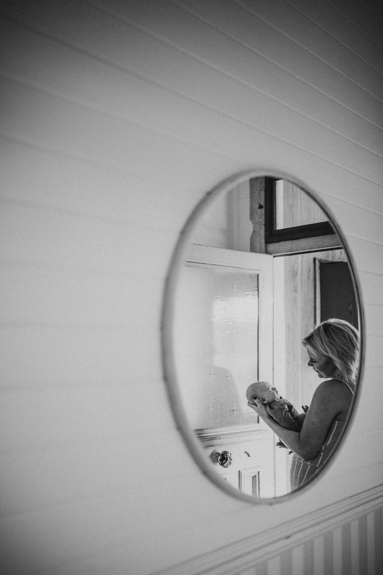 Black and white view of mother and baby in a mirror