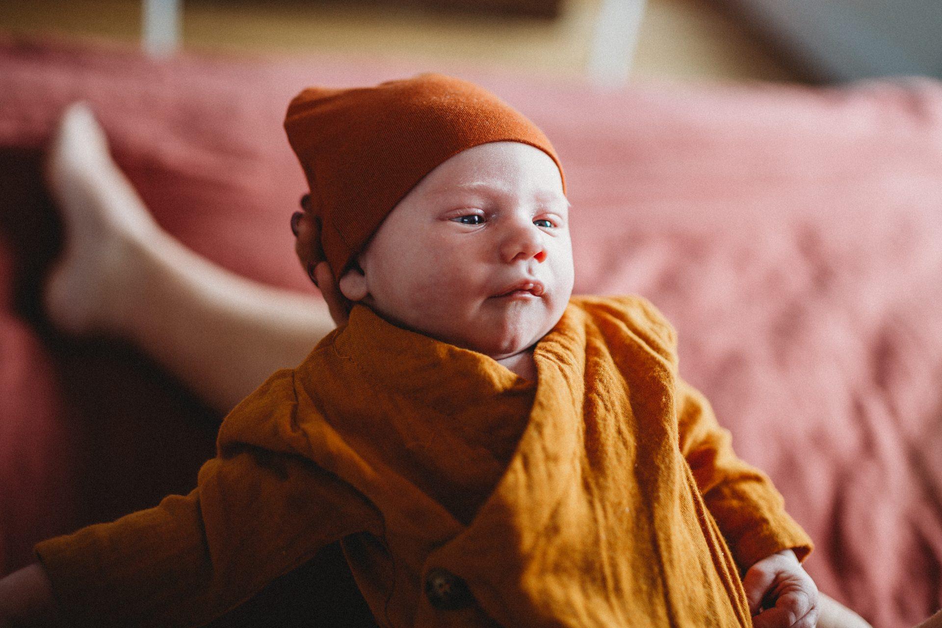 Newborn baby boy dressed in orange beanie and onesie, being held in mother's hands