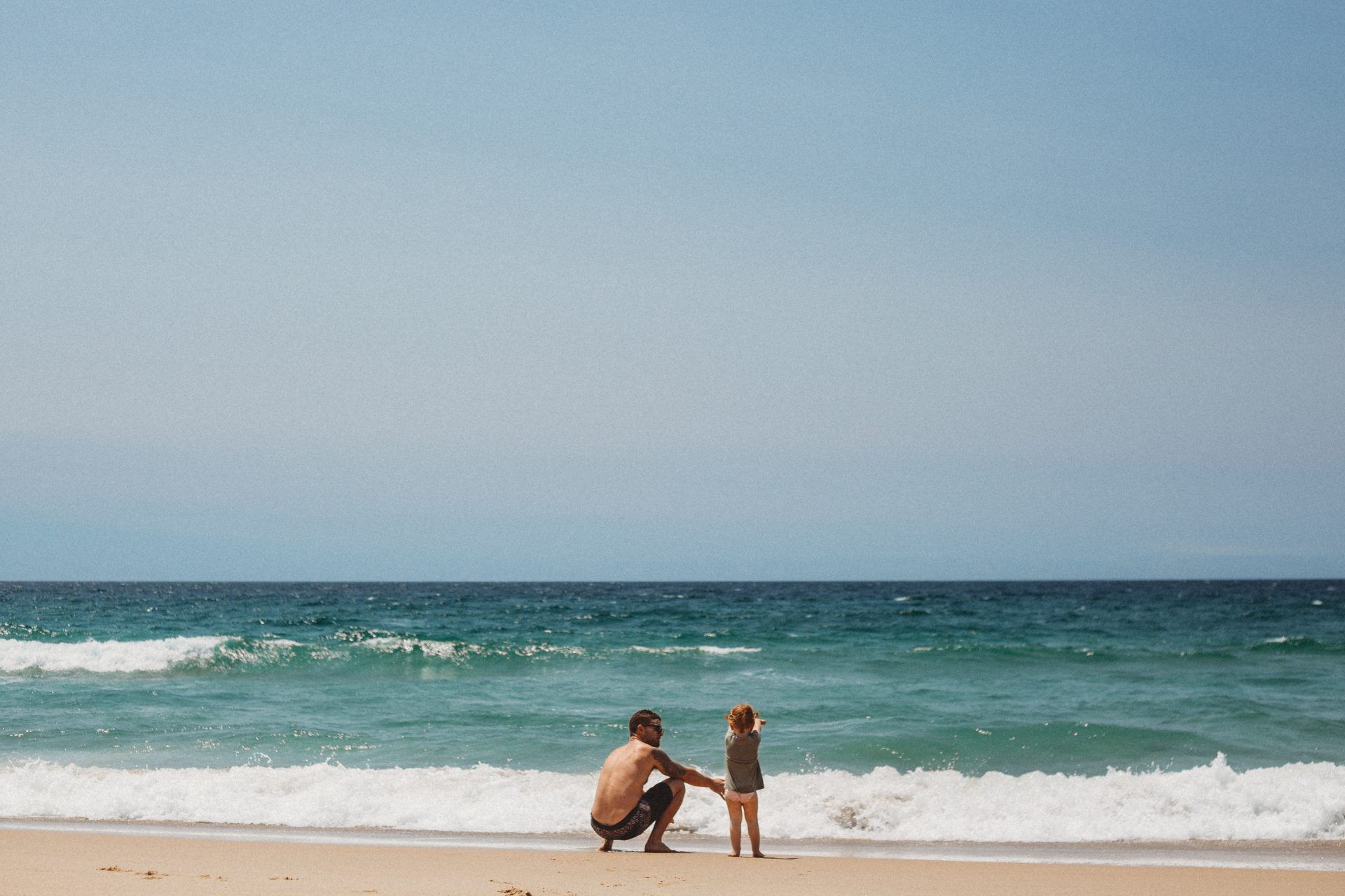 Father and daughter play at the beach