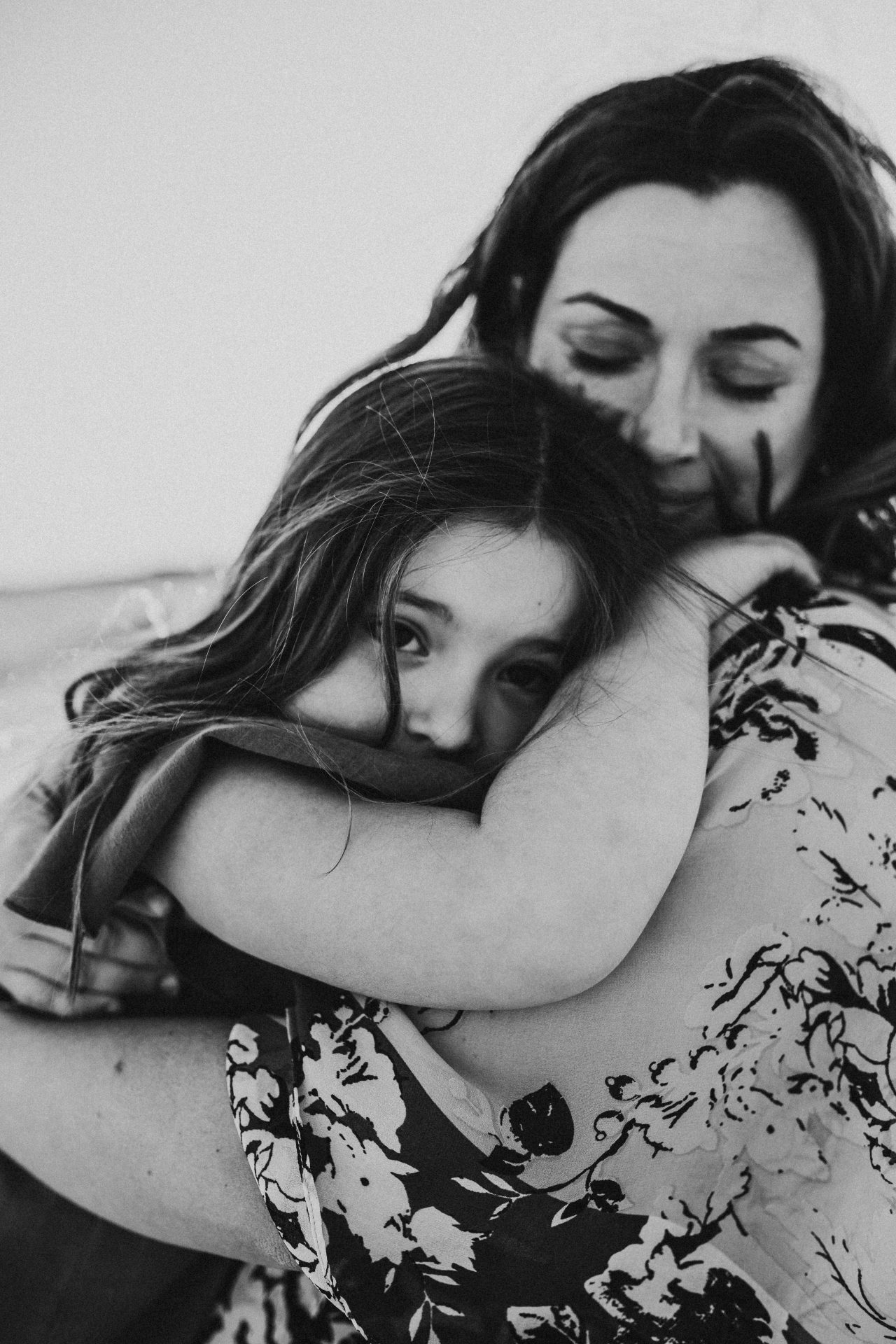 Black and white image of mother hugging her young daughter