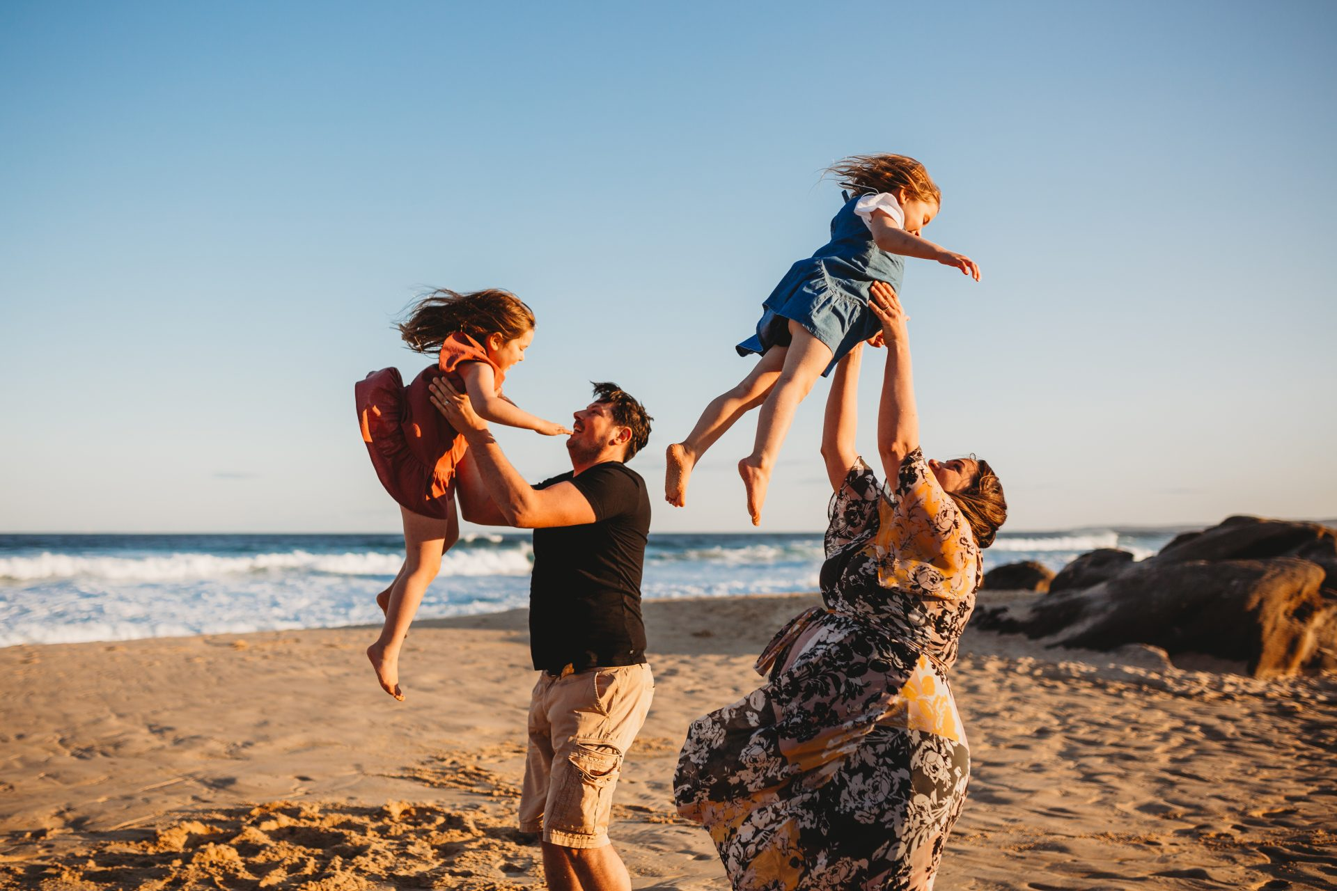 Mother and father throwing their young daughters up into the air, at the beach