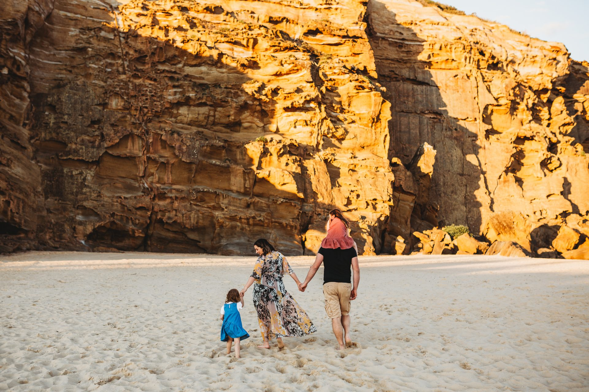 Family walking away from camera, on the beach towards cliff face, while holding hands
