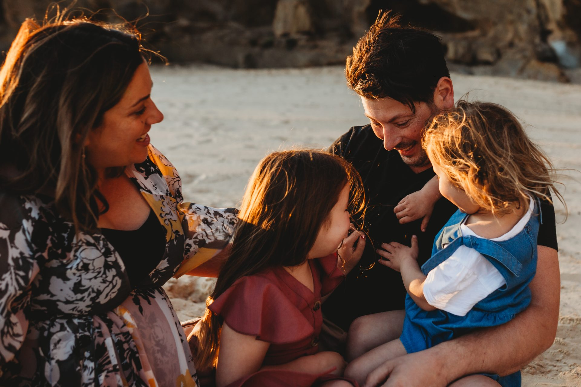 Young family huddled together on the beach at sunset, sitting on the sand, laughing and tickling