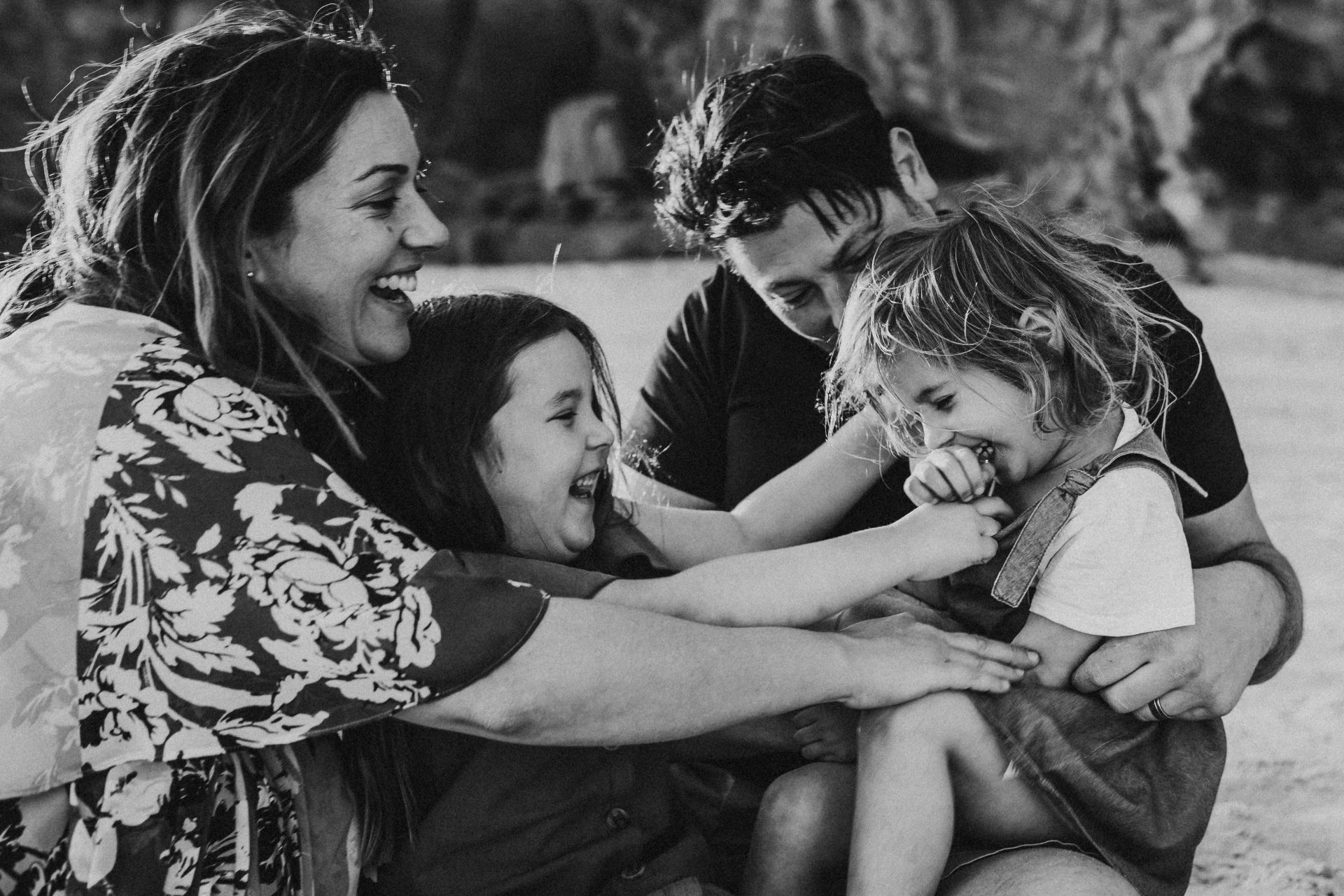 Black and white image of family huddled together on the beach at sunset, sitting on the sand, laughing and tickling