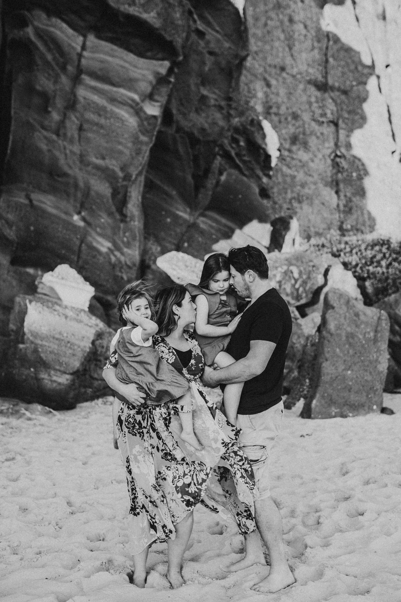 Black and white image of family standing on the beach, cuddling