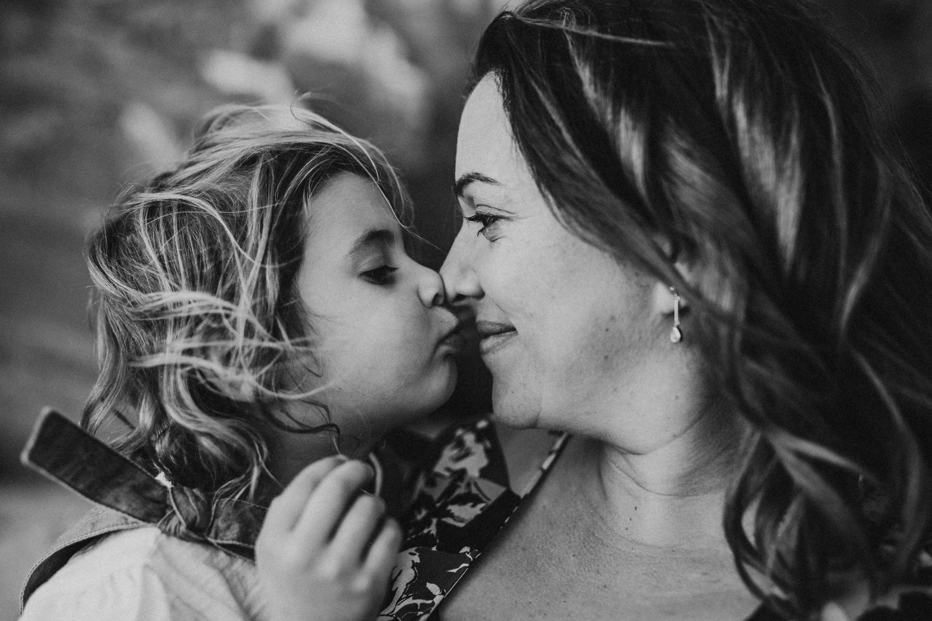 Black and white image of woman and her daughter touching noses