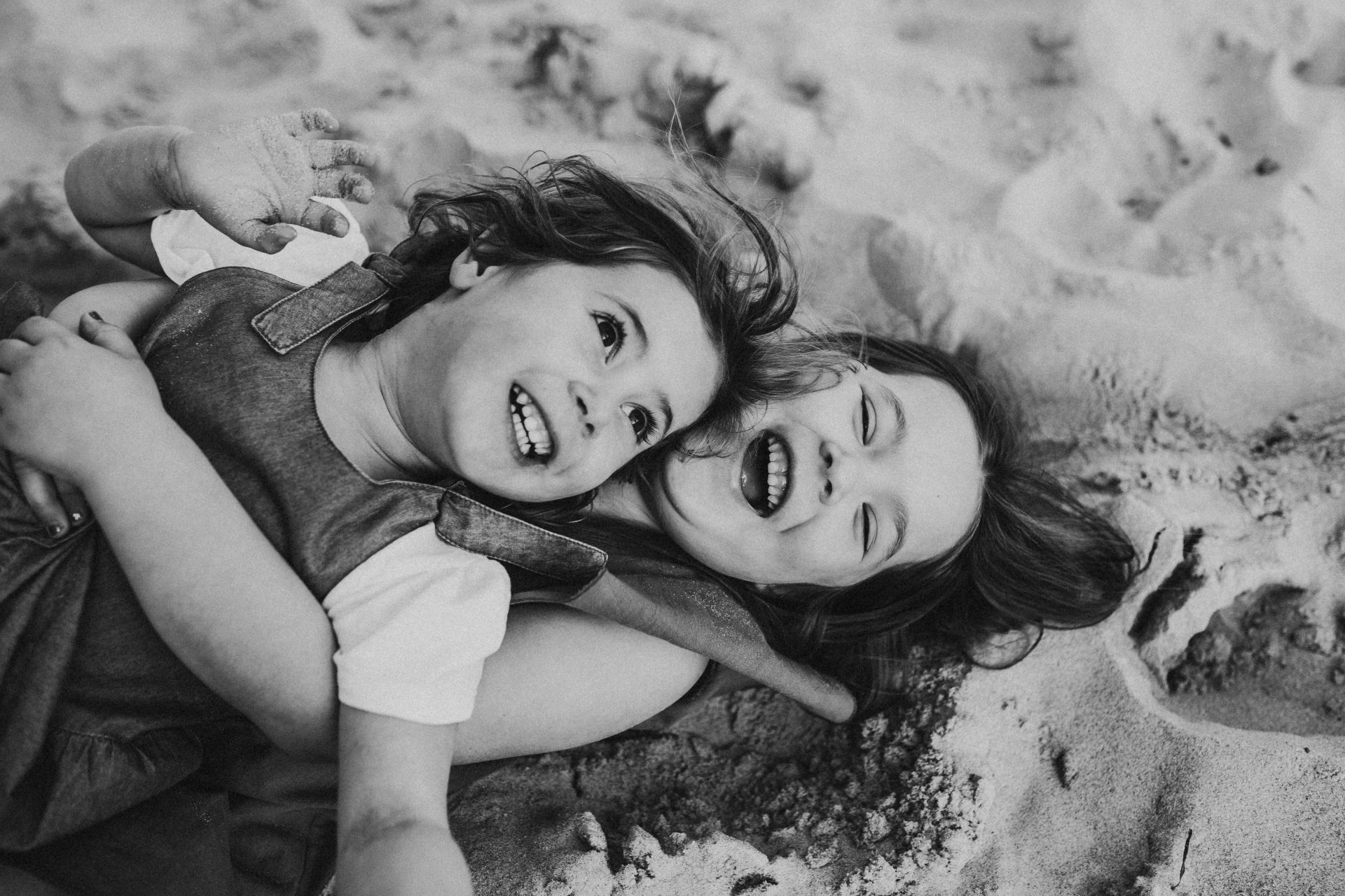 Young sisters laying on each other at the beach, laughing