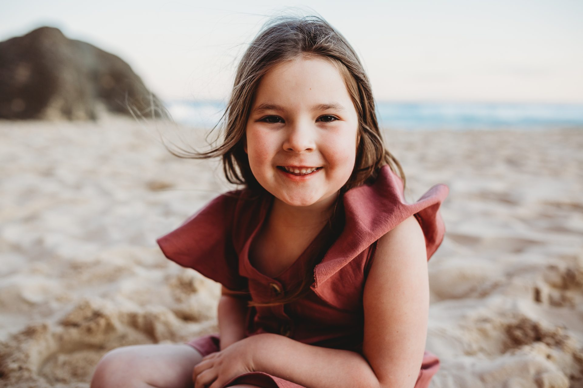 Little girl wearing pink dress, smiling at the camera while sitting on the beach