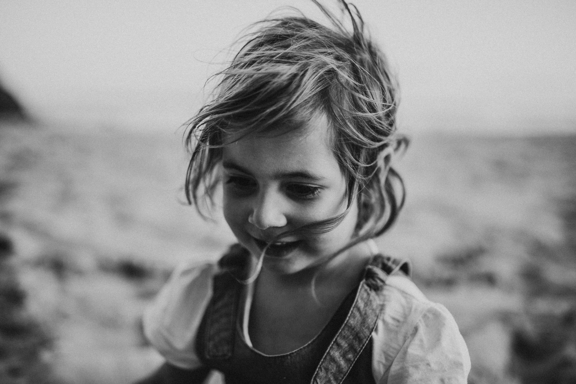 Black and white image of little girl with windswept hair