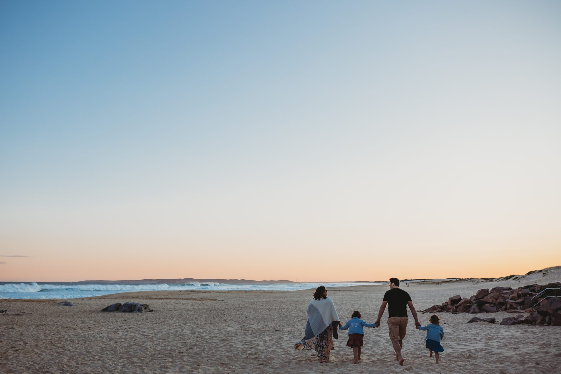 Family walking away from camera, holding hands on the beach at sunset