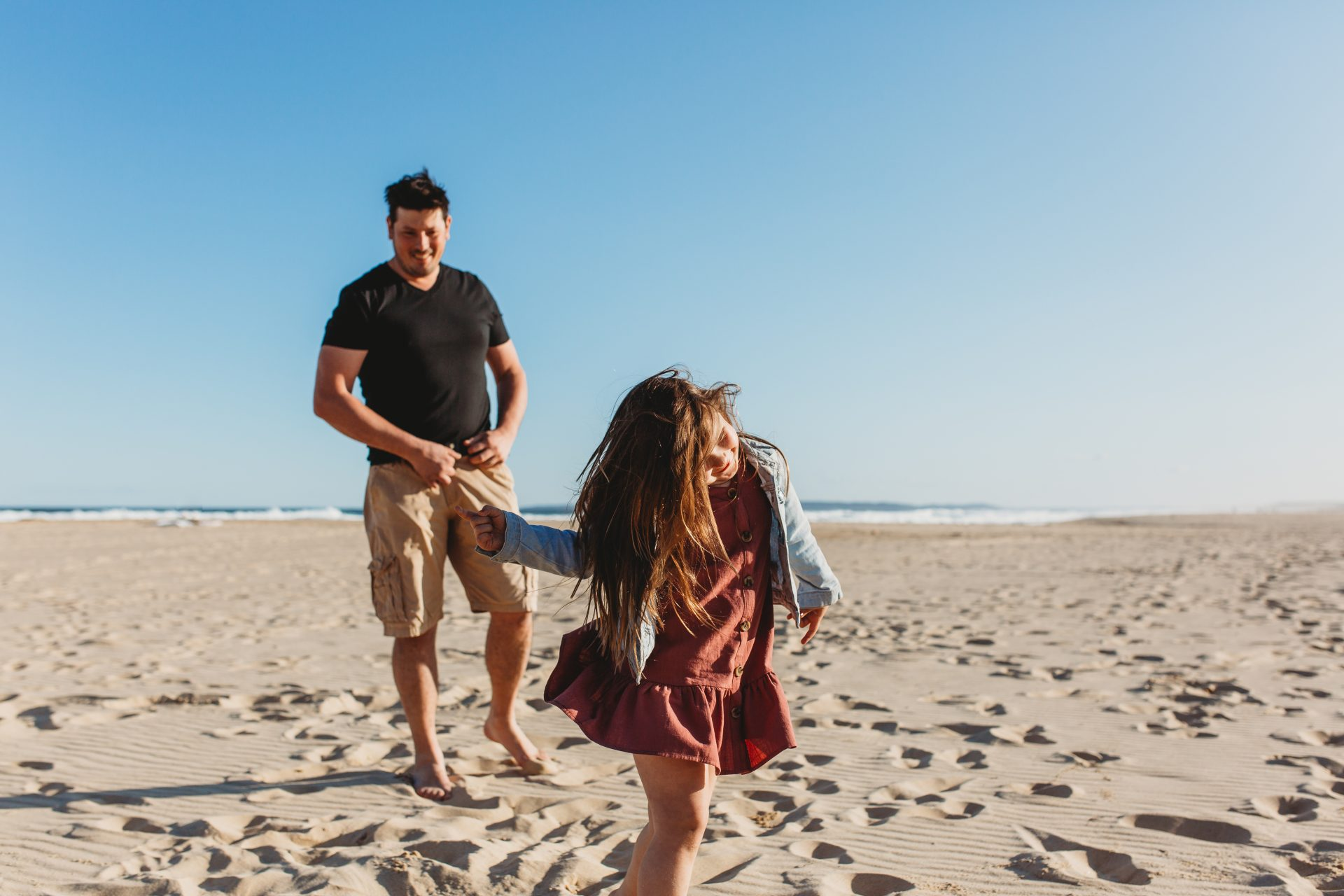 Young girl dancing on the sand while her dad watches on