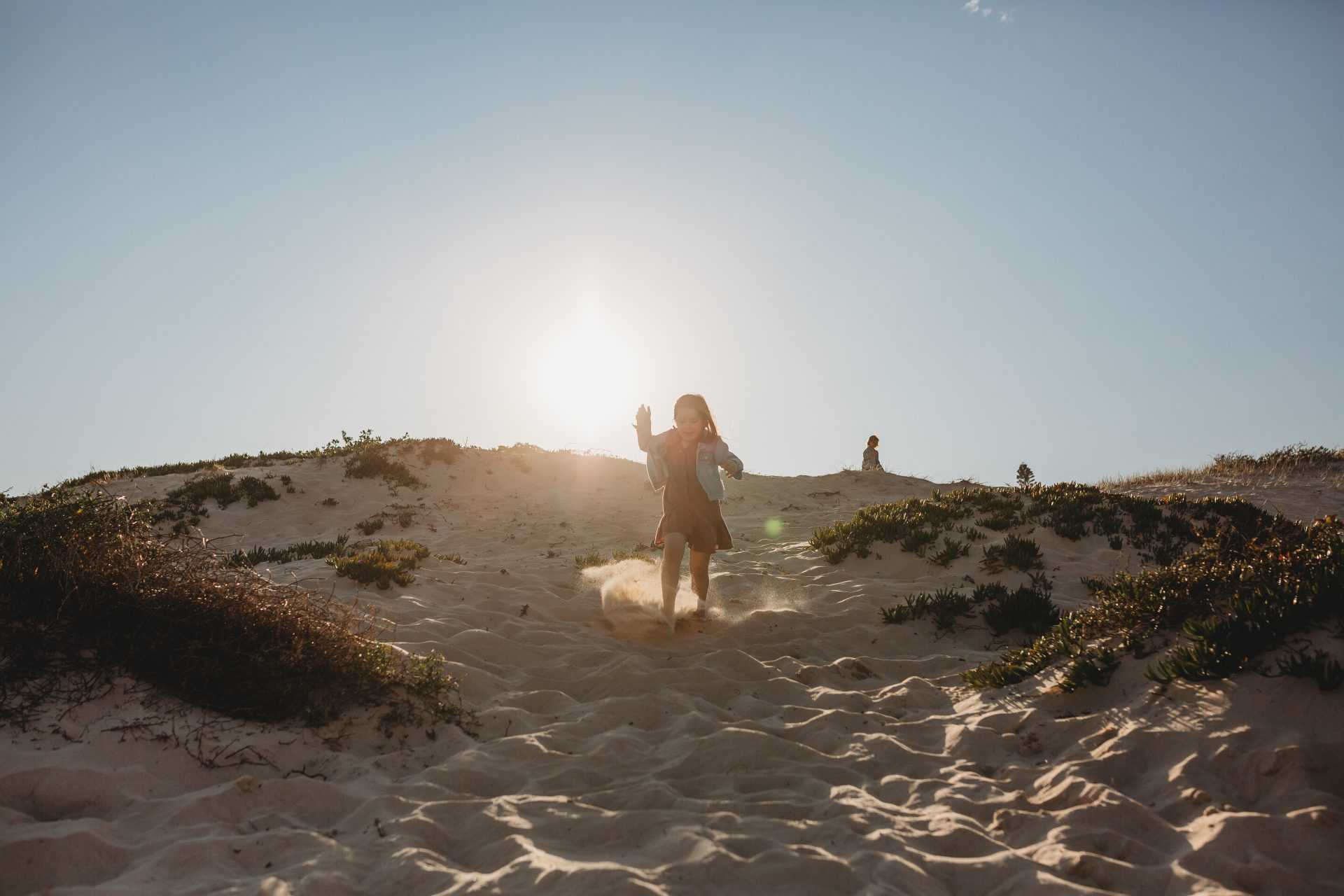 Young girl running down a sand dune towards the camera