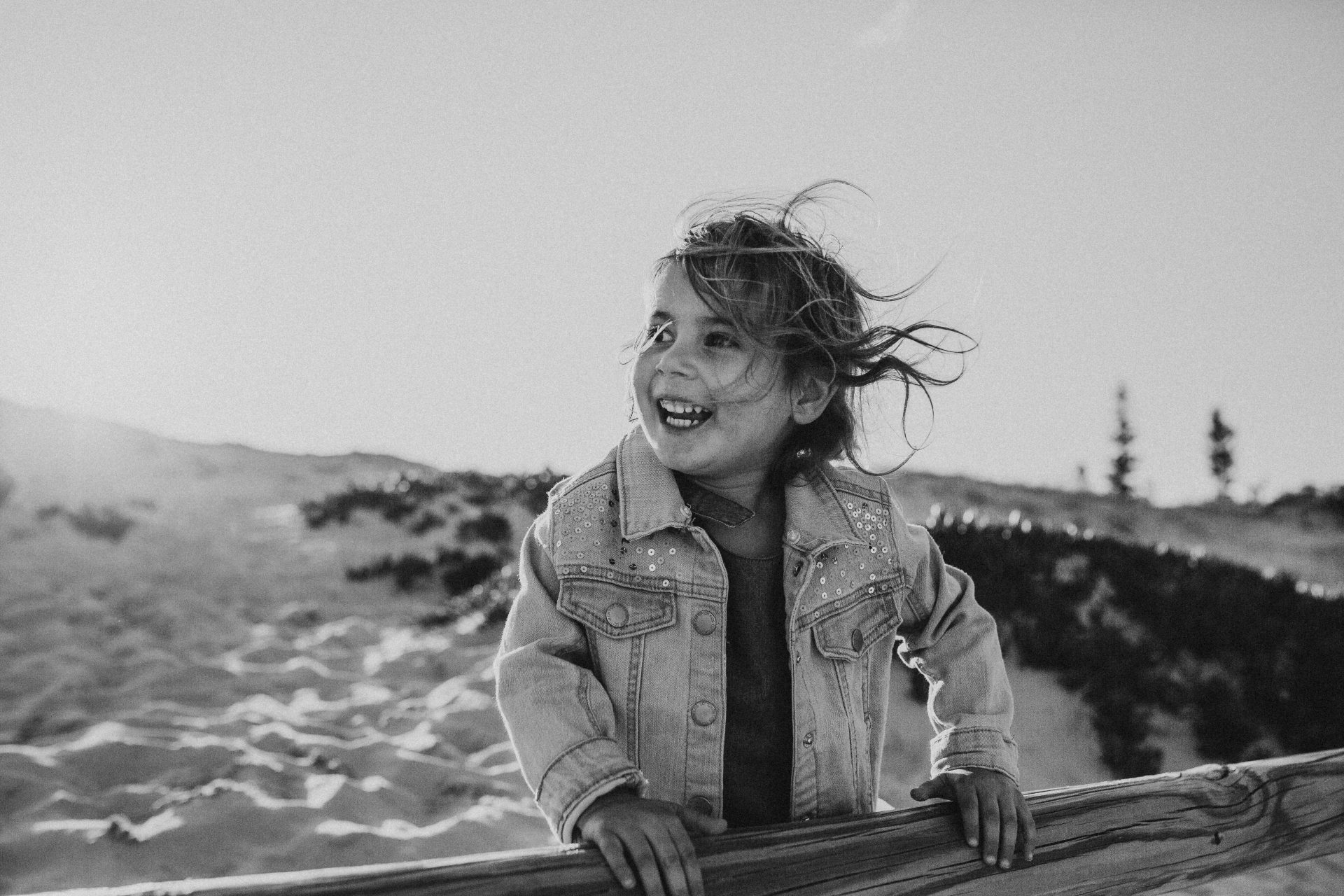 Black and white image of little girl in denim jacket, smiling with her hair blowing in the wind