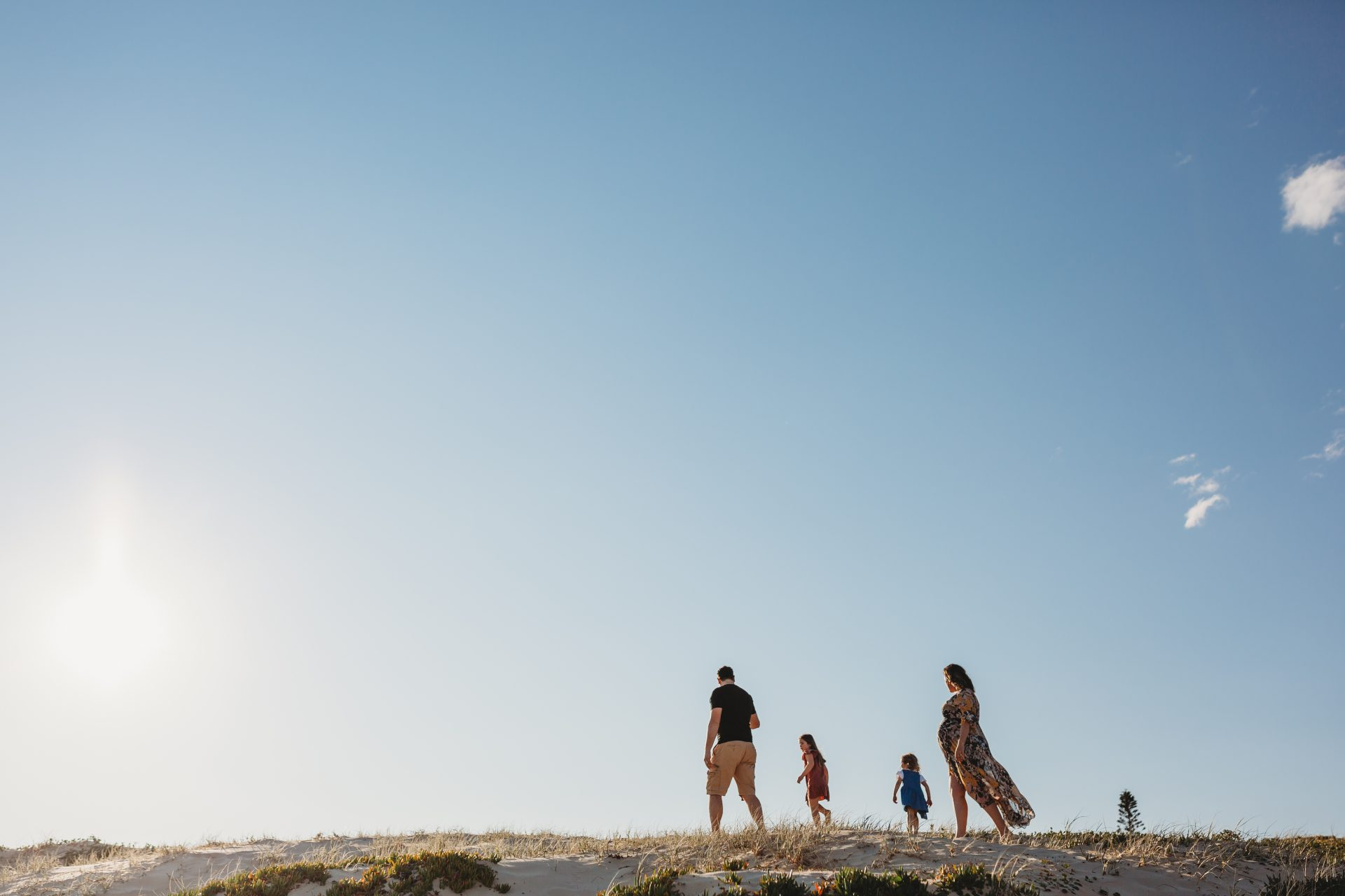 Family walking along the sand, in single file