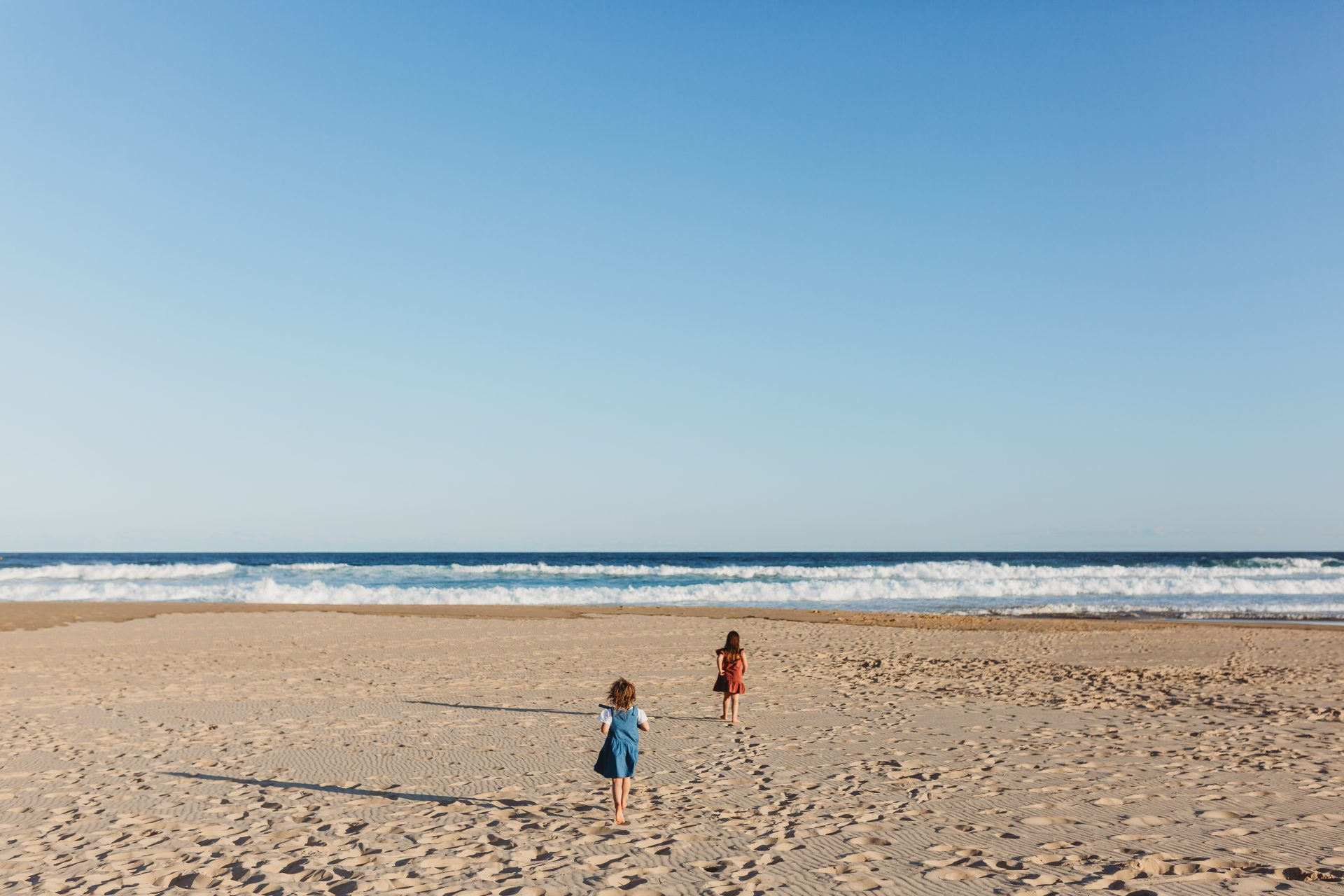 Two young sisters run towards the ocean, away from the photographer
