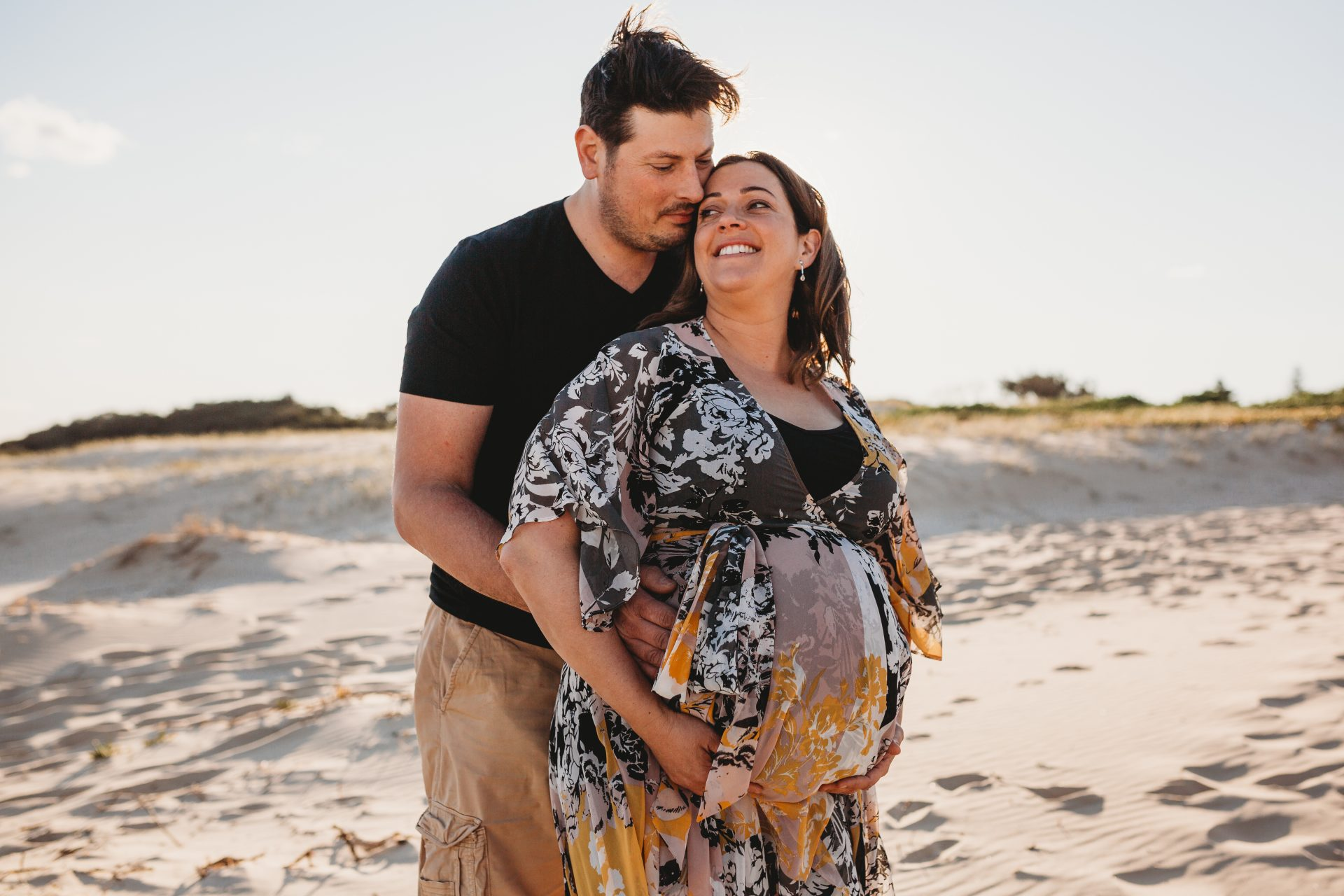 Pregnant woman standing in front of her husband smiling, as he cuddles her from behind