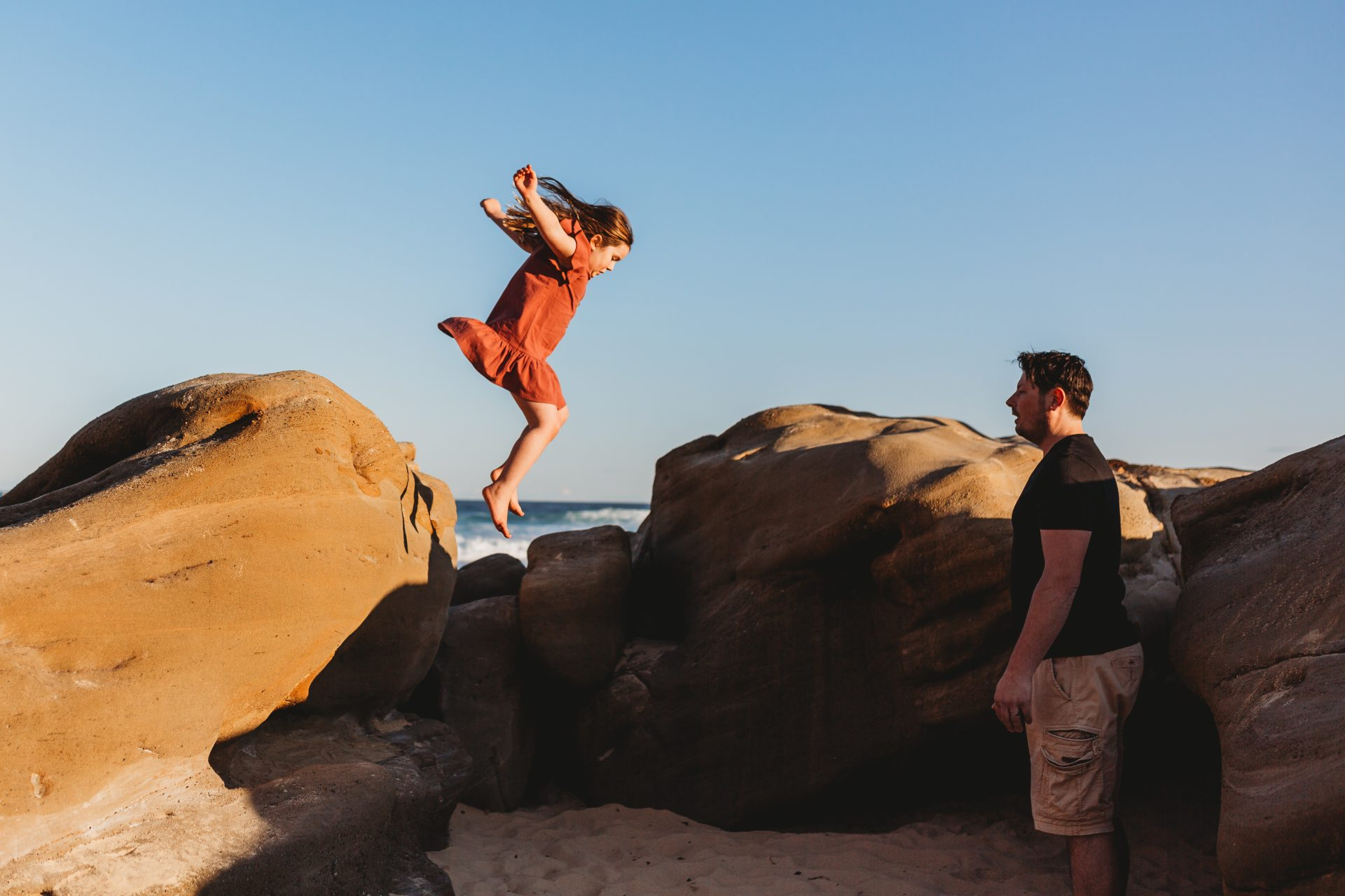 Little girl jumping off a rock to her father