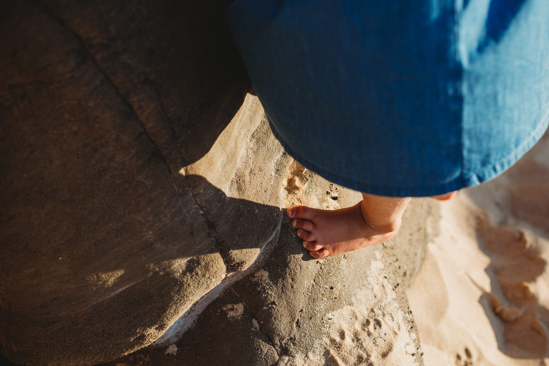 Close up of little girl's foot while climbing a rock