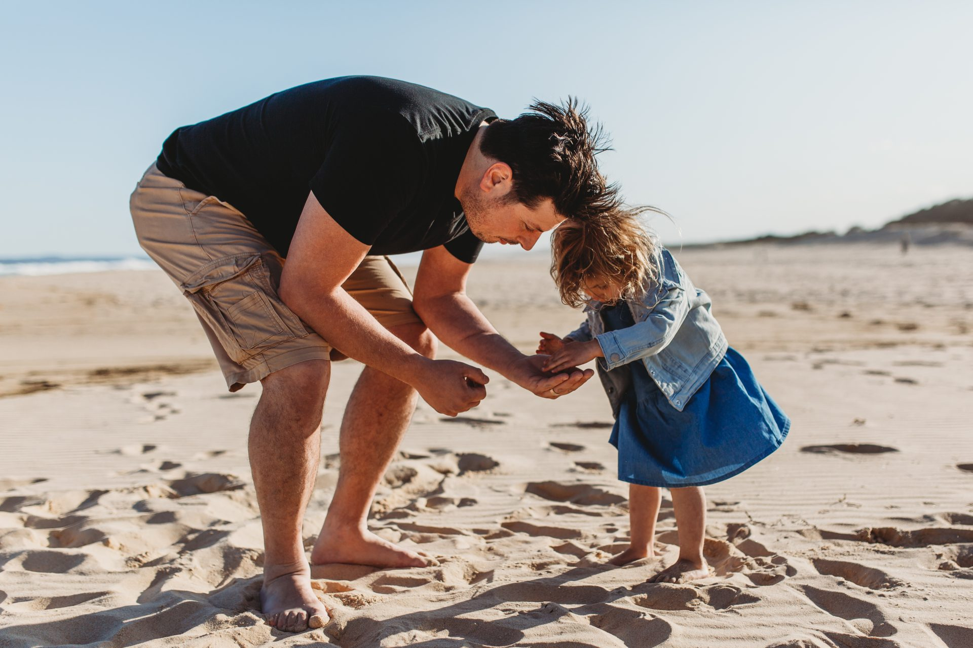 Young girl with father looking at shells on the sand