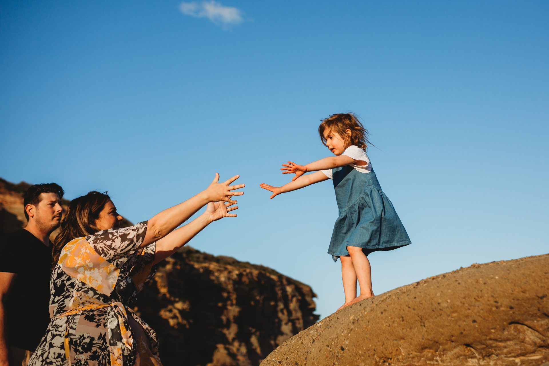 Little girl on a large rock, reaching out towards her mother who also has her arms reaching for her daughter
