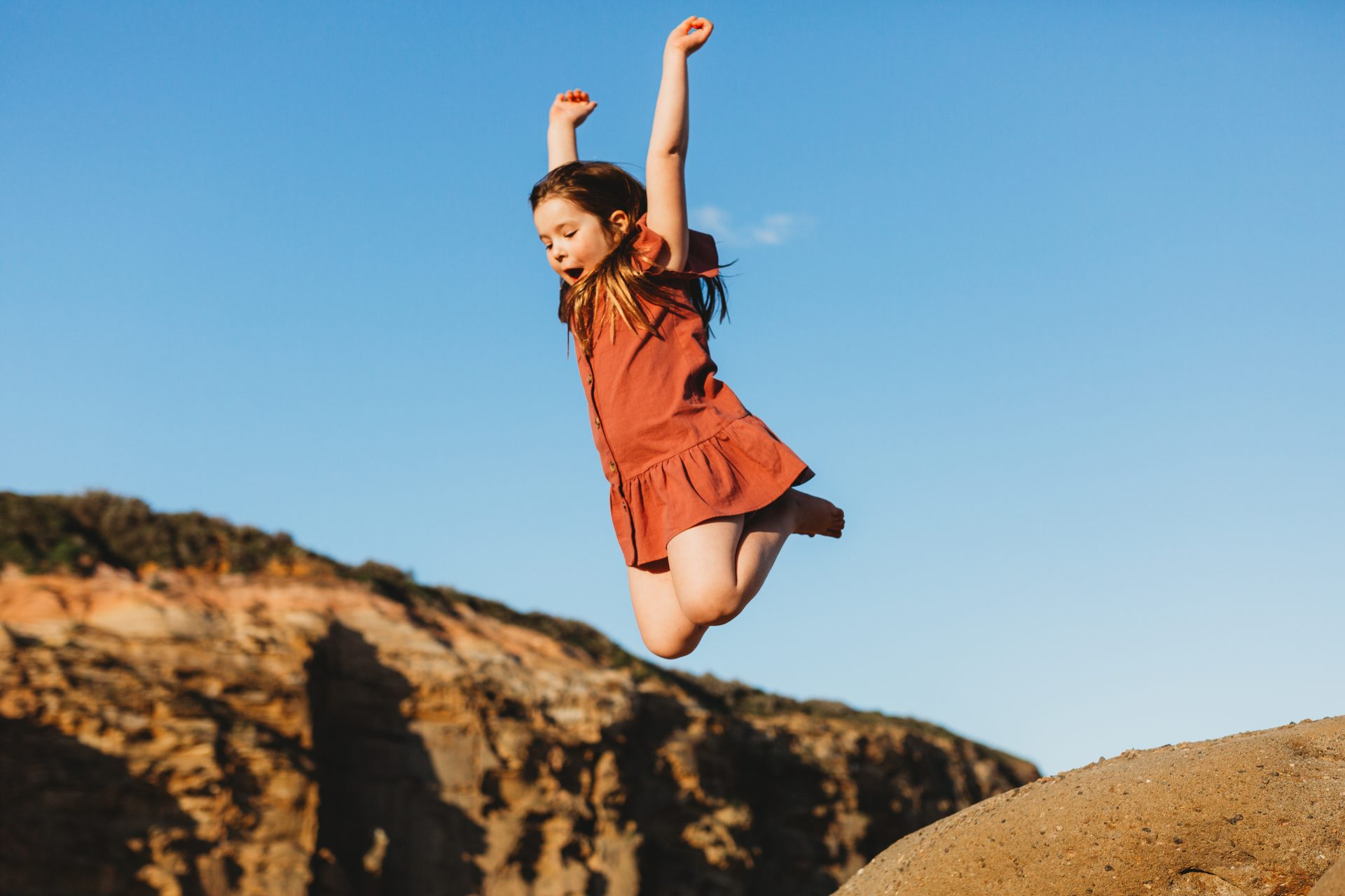 Young girl jumping off a large rock, with her arms up in the air