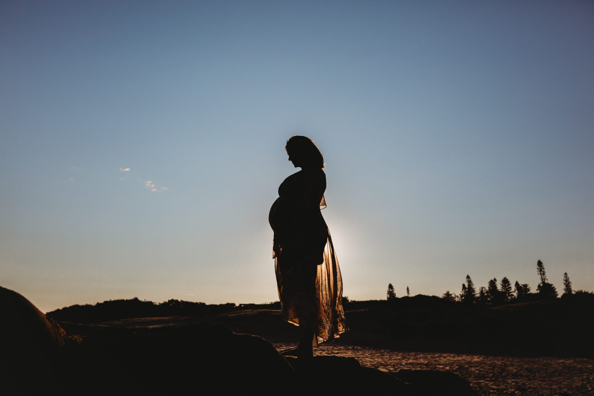 Pregnant woman silhouetted against a late afternoon sky